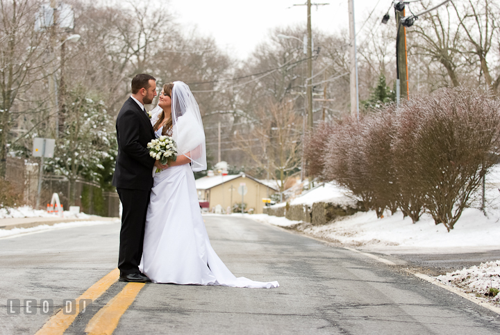 Bride and Groom cuddling in a wintry backdrop town. The Ballroom at The Chesapeake Inn wedding ceremony photos, Chesapeake City, Maryland by photographers of Leo Dj Photography.
