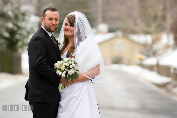Bride and Groom posing on a road covered with snow. The Ballroom at The Chesapeake Inn wedding ceremony photos, Chesapeake City, Maryland by photographers of Leo Dj Photography.