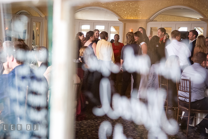 Guests dancing seen through a window. The Ballroom at The Chesapeake Inn wedding reception photos, Chesapeake City, Maryland by photographers of Leo Dj Photography.