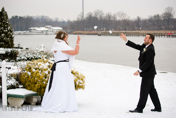 Bride and Groom throwing snowball at each other. The Ballroom at The Chesapeake Inn wedding reception photos, Chesapeake City, Maryland by photographers of Leo Dj Photography.