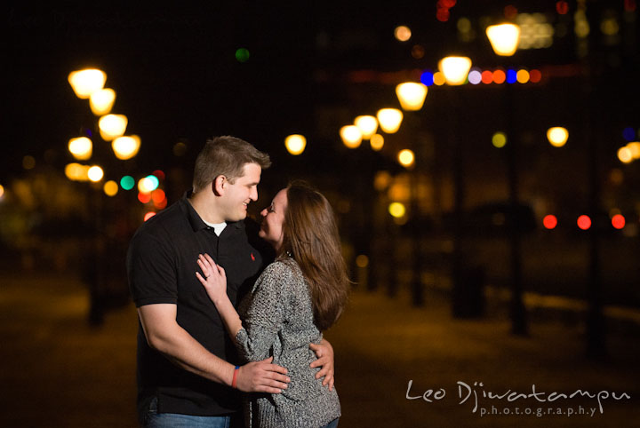 Engaged couple embracing each other in the evening. Fells Point Baltimore Maryland pre-wedding engagement photo session with their dog pet by wedding photographers of Leo Dj Photography