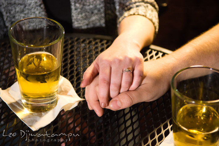 Engaged couple holding hands showing the wedding ring with glasses of beers