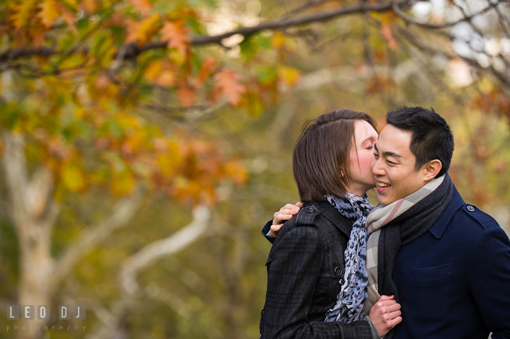 Engaged girl kissing her fiancé at Central Park. Pre-wedding engagement photo session at New York City, NY, by wedding photographers of Leo Dj Photography. http://leodjphoto.com
