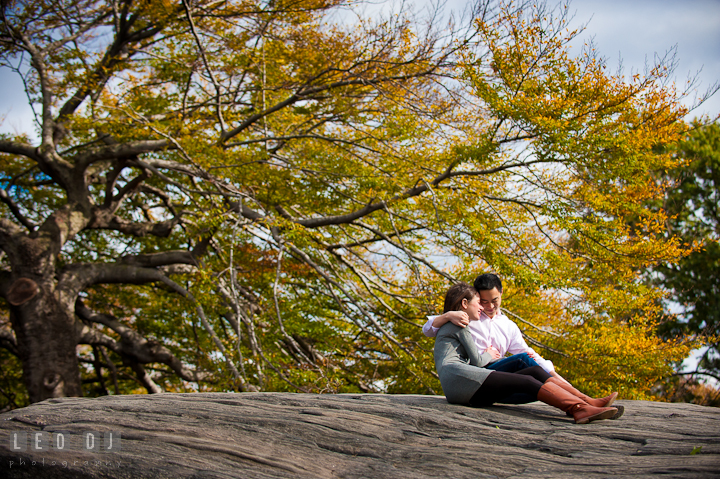 Engaged guy cuddling his fiancée on a huge rock at Central Park. Pre-wedding engagement photo session at New York City, NY, by wedding photographers of Leo Dj Photography. http://leodjphoto.com