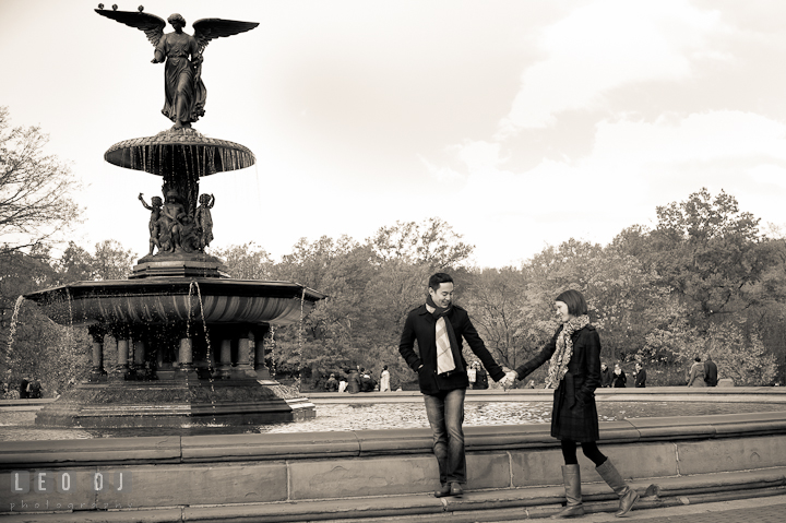 Engaged couple walking by the fountain at Bethesda Terrace, Central Park. Pre-wedding engagement photo session at New York City, NY, by wedding photographers of Leo Dj Photography. http://leodjphoto.com