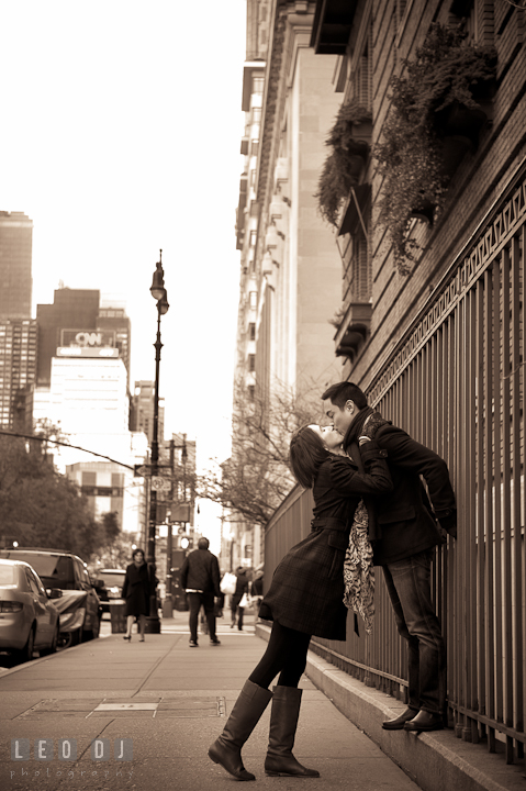 Engaged guy and girl kissing on the street sidewalk by the CNN building. Pre-wedding engagement photo session at New York City, NY, by wedding photographers of Leo Dj Photography. http://leodjphoto.com