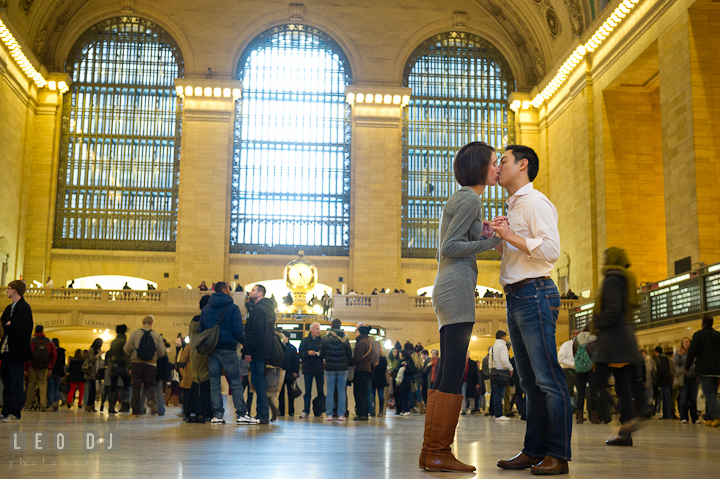 Engaged guy and girl kissing inside the Grand Central Station. Pre-wedding engagement photo session at New York City, NY, by wedding photographers of Leo Dj Photography. http://leodjphoto.com