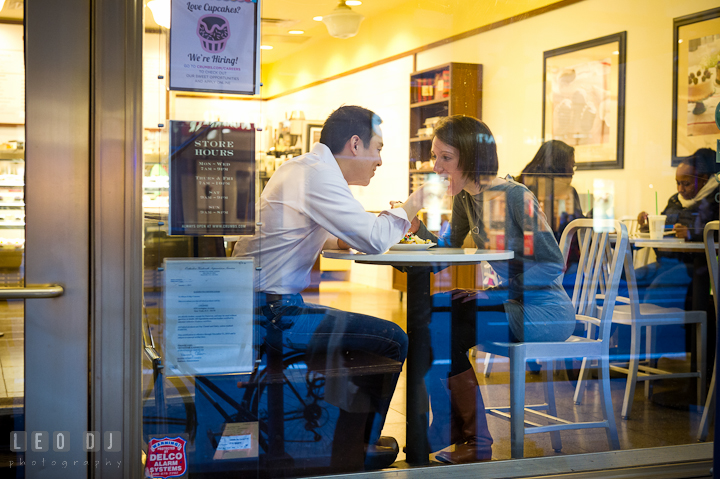 Engaged couple feeding cup cakes to each other at a cafe by Grand Central. Pre-wedding engagement photo session at New York City, NY, by wedding photographers of Leo Dj Photography. http://leodjphoto.com