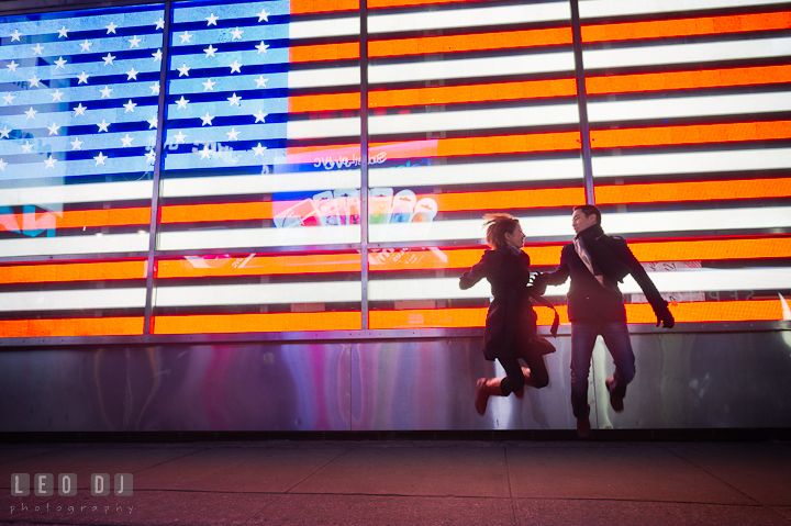 Engaged guy and girl jumping in front of an American flag light display. Pre-wedding engagement photo session at New York City, NY, by wedding photographers of Leo Dj Photography. http://leodjphoto.com