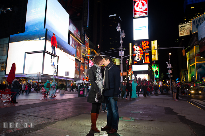 Engaged guy and girl cuddling at the Times Square. Pre-wedding engagement photo session at New York City, NY, by wedding photographers of Leo Dj Photography. http://leodjphoto.com