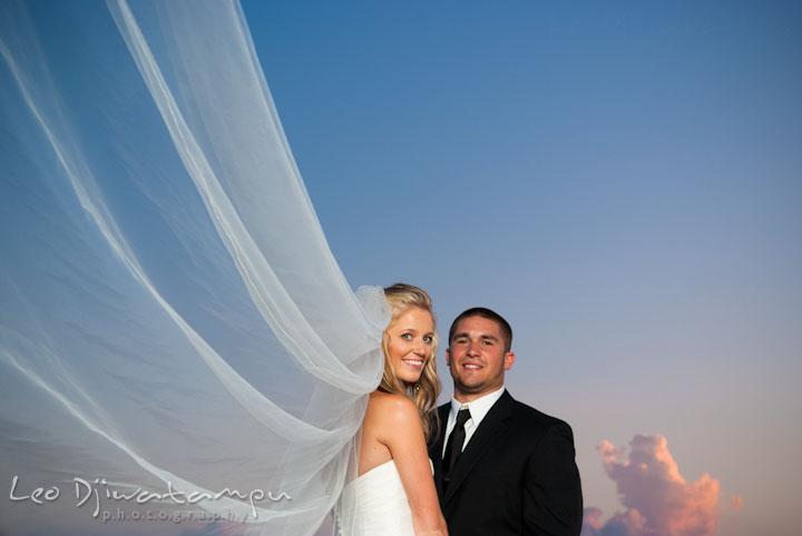 Bride with long veil and groom holding hands with sunset sky. Silver Swan Bayside Wedding Photos, Stevensville, Eastern Shore Maryland by wedding photographers of Leo Dj Photography