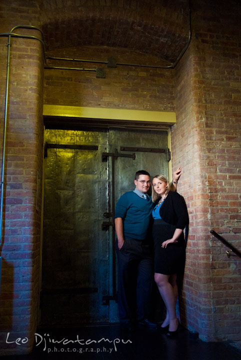 Engaged couple posing by an industrial metal door. Ellicott City and Patapsco Park Maryland pre-wedding engagement photo session by photographers of Leo Dj Photography
