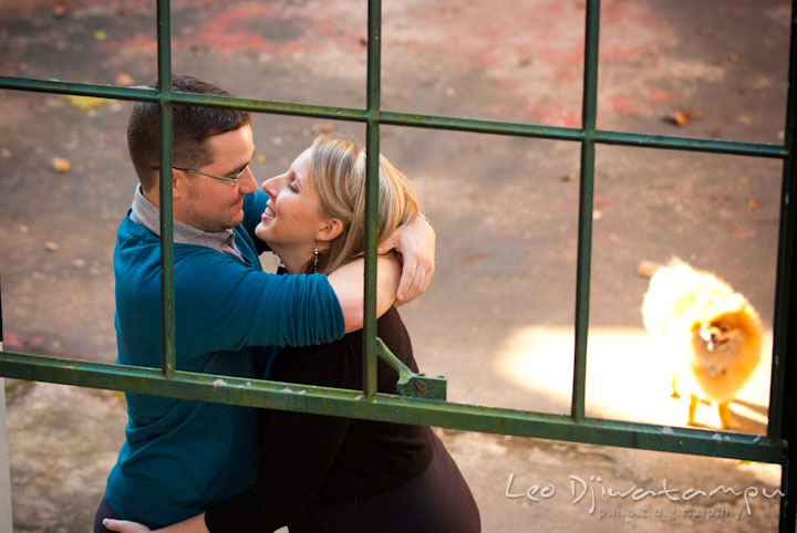 Engaged couple hugging. Their dog looking. Ellicott City and Patapsco Park Maryland pre-wedding engagement photo session by photographers of Leo Dj Photography