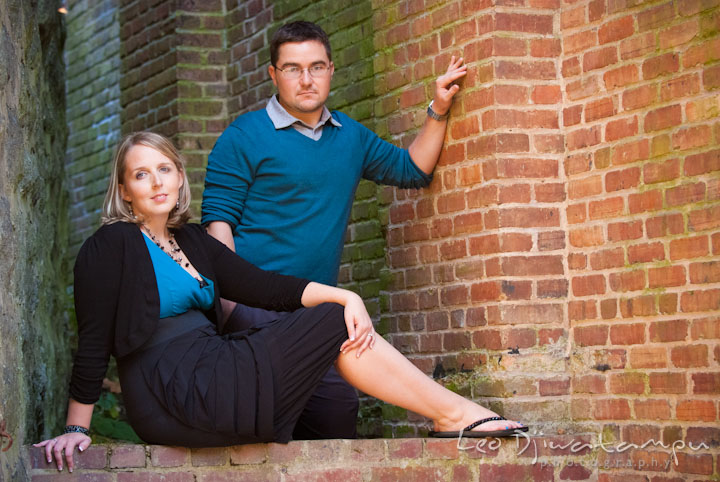 Engaged guy and girl posing by a brick structure. Ellicott City and Patapsco Park Maryland pre-wedding engagement photo session by photographers of Leo Dj Photography