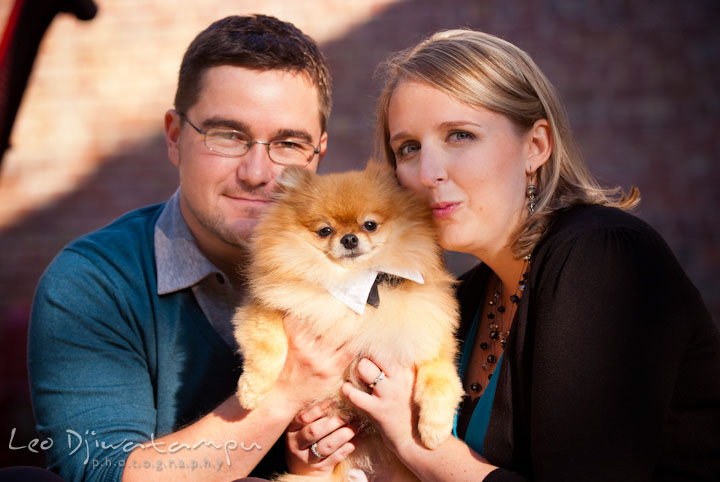 Engaged couple posing with their dog. Ellicott City and Patapsco Park Maryland pre-wedding engagement photo session by photographers of Leo Dj Photography