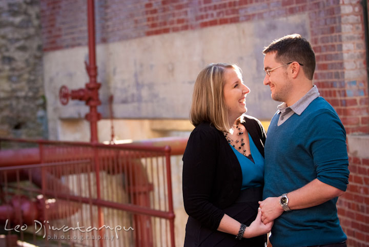 Engaged guy and girl looking at each other and smiling. Ellicott City and Patapsco Park Maryland pre-wedding engagement photo session by photographers of Leo Dj Photography