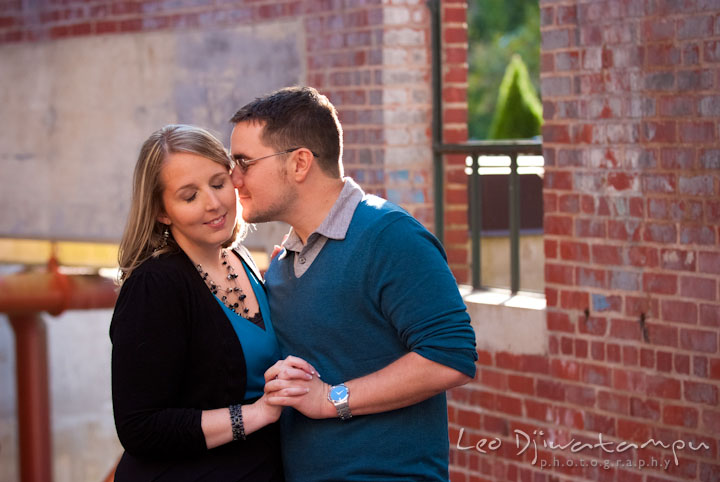 Engaged guy kissing his fiancée. Ellicott City and Patapsco Park Maryland pre-wedding engagement photo session by photographers of Leo Dj Photography