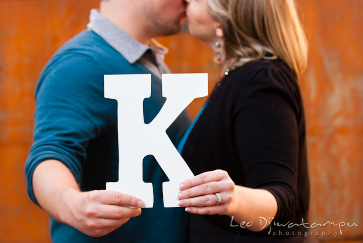 Engaged couple kissing while holding letter K and showing engagement ring. Ellicott City and Patapsco Park Maryland pre-wedding engagement photo session by photographers of Leo Dj Photography