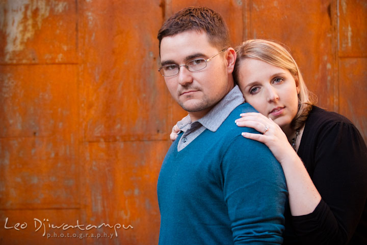 Engaged girl leaning on her fiancé's back. Ellicott City and Patapsco Park Maryland pre-wedding engagement photo session by photographers of Leo Dj Photography