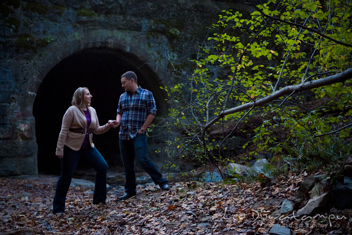 Engaged couple holding hands by a tunnel in the woods. Ellicott City and Patapsco Park Maryland pre-wedding engagement photo session by photographers of Leo Dj Photography