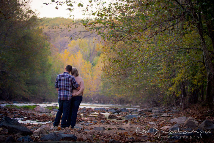 Engaged guy hugging his fiancée overlooking at the river. Ellicott City and Patapsco Park Maryland pre-wedding engagement photo session by photographers of Leo Dj Photography