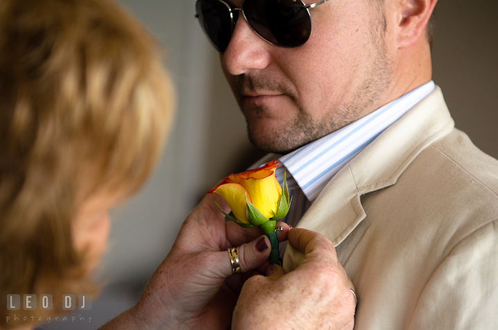Mother of groom helping son putting on boutonniere. Cruise ship destination wedding ceremony photos, Hotel Melia Cozumel Mexico by photographers of Leo Dj Photography.