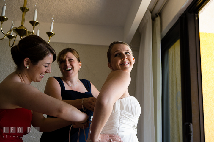 Matron of Honor and mother helping brid putting on wedding dress. Cruise ship destination wedding ceremony photos, Hotel Melia Cozumel Mexico by photographers of Leo Dj Photography.