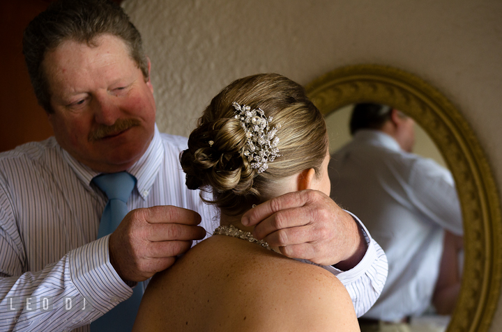 Father of the Bride helping daughter putting on the necklace. Cruise ship destination wedding ceremony photos, Hotel Melia Cozumel Mexico by photographers of Leo Dj Photography.
