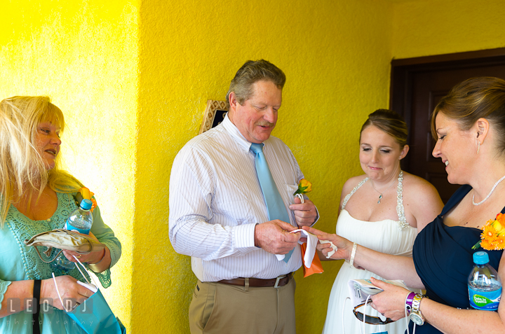 Mother handing out handkerchief gift to Father of the Bride. Cruise ship destination wedding ceremony photos, Hotel Melia Cozumel Mexico by photographers of Leo Dj Photography.