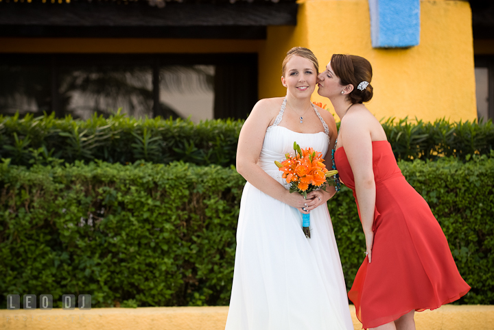 Matron of Honor trying to kiss Bride's cheek. Cruise ship destination wedding ceremony photos, Hotel Melia Cozumel Mexico by photographers of Leo Dj Photography.