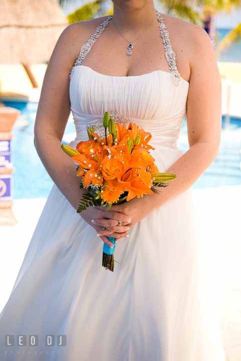 Bride's orang floral bouquet. Cruise ship destination wedding ceremony photos, Hotel Melia Cozumel Mexico by photographers of Leo Dj Photography.