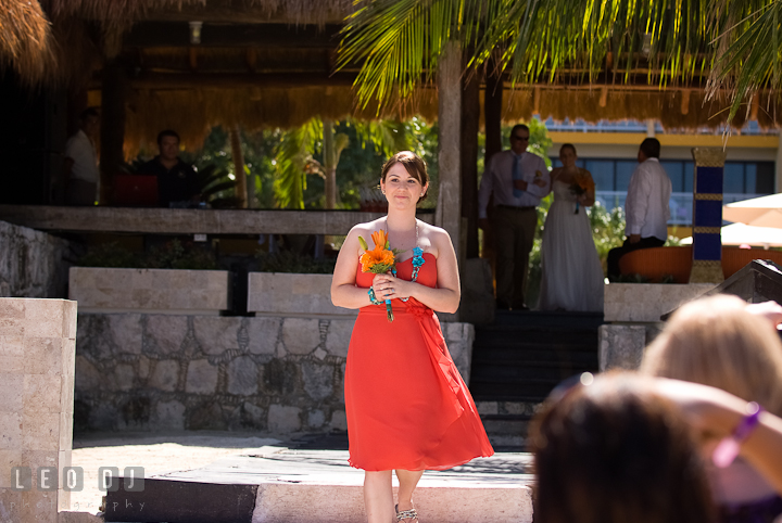 Matron of Honor walking down the isle. Cruise ship destination wedding ceremony photos, Hotel Melia Cozumel Mexico by photographers of Leo Dj Photography.