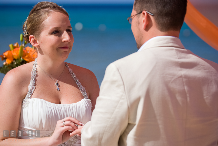 Bride putting on wedding band on Groom's finger. Cruise ship destination wedding ceremony photos, Hotel Melia Cozumel Mexico by photographers of Leo Dj Photography.