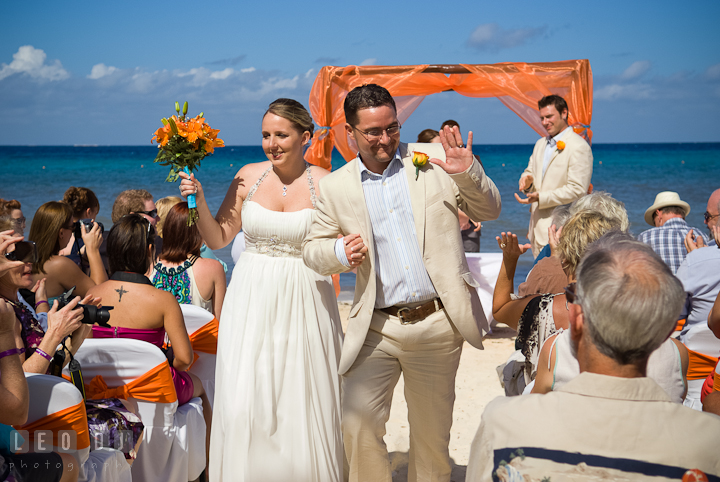 Bride and Groom waved to guests as the walked out from the ceremony site. Cruise ship destination wedding ceremony photos, Hotel Melia Cozumel Mexico by photographers of Leo Dj Photography.