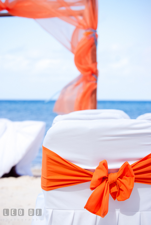 Orang decoration accents for ceremony chairs and canopy. Cruise ship destination wedding ceremony photos, Hotel Melia Cozumel Mexico by photographers of Leo Dj Photography.