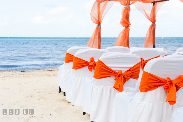 Ceremony chairs with orange ribbons overlooking at the blue sea. Cruise ship destination wedding ceremony photos, Hotel Melia Cozumel Mexico by photographers of Leo Dj Photography.