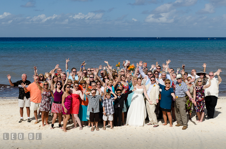 Group shot on the beach. Carnival Cruise ship destination wedding reception photos of Jessica and Chad, Cozumel Mexico by photographers of Leo Dj Photography.