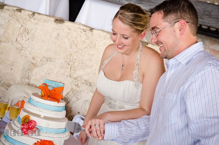 Bride and Groom smiling cutting the cake. Carnival Cruise ship destination wedding reception photos of Jessica and Chad, Cozumel Mexico by photographers of Leo Dj Photography.