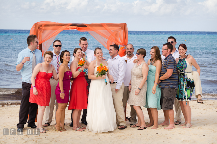 Group shot with the Bride and Groom by the orange canopy on the beach. Carnival Cruise ship destination wedding reception photos of Jessica and Chad, Cozumel Mexico by photographers of Leo Dj Photography.