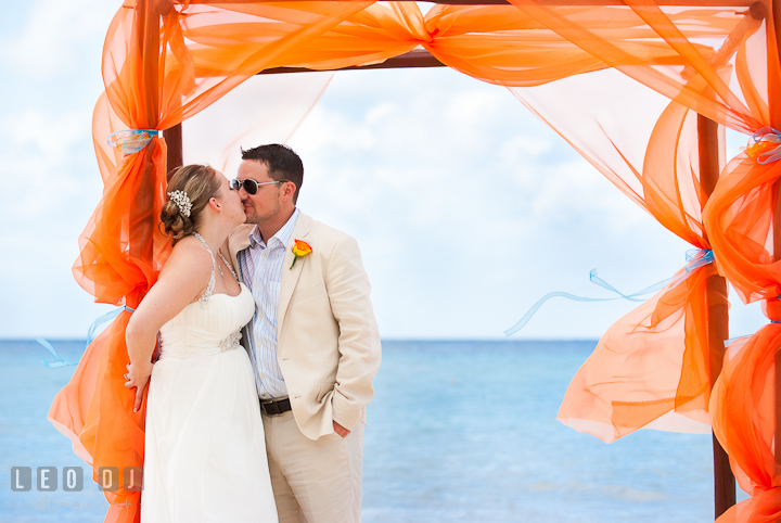 Bride and groom kissing under a canopy on the beach. Cruise ship destination wedding ceremony photos, Hotel Melia Cozumel Mexico by photographers of Leo Dj Photography.