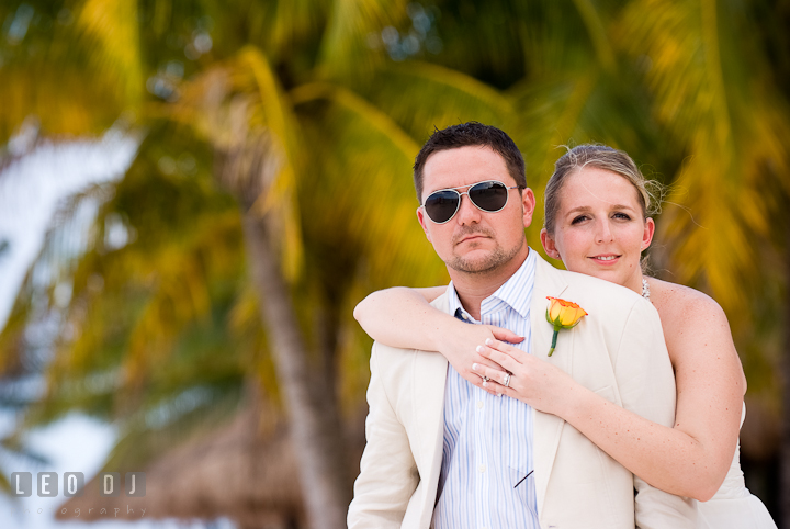 Bride and Groom cuddling by palm trees on the beach. Carnival Cruise ship d