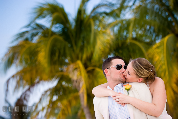 Bride and Groom kissed on the beach, by the palm trees. Carnival Cruise ship destination wedding reception photos of Jessica and Chad, Cozumel Mexico by photographers of Leo Dj Photography.
