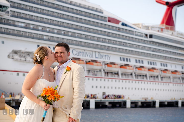 Bride kissed Groom by the ship. Carnival Cruise ship destination wedding reception photos of Jessica and Chad, Cozumel Mexico by photographers of Leo Dj Photography.