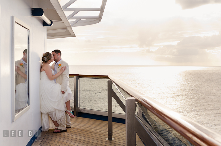 Bride and Groom kissing on the balcony outside their room. Carnival Cruise ship destination wedding reception photos of Jessica and Chad, Cozumel Mexico by photographers of Leo Dj Photography.