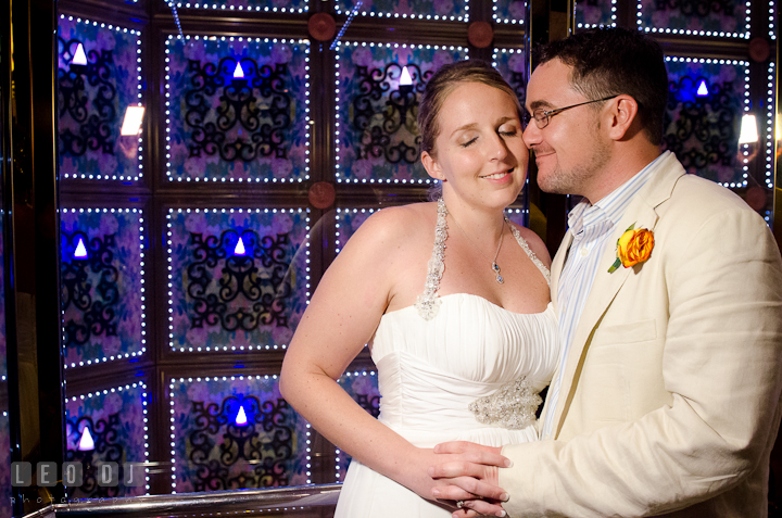 Bridge and Groom cuddling by glass elevator in the cruise ship. Carnival Cruise ship destination wedding reception photos, Cozumel Mexico by photographers of Leo Dj Photography.