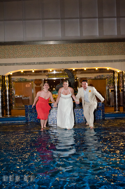 Bride, Groom and Maid of Honor getting ready to jump into swimming pool to trash the dress. Carnival Cruise ship destination wedding reception photos, Cozumel Mexico by photographers of Leo Dj Photography.