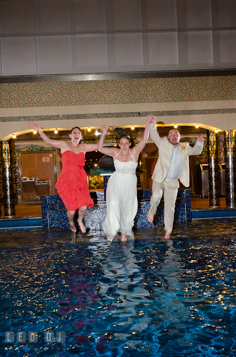 Bride, Groom and Maid of Honor starting to jump into swimming pool to trash the dress. Carnival Cruise ship destination wedding reception photos, Cozumel Mexico by photographers of Leo Dj Photography.