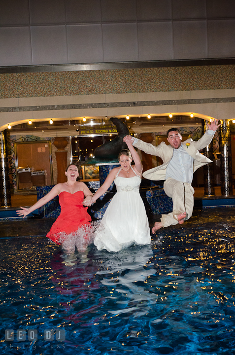 Bride, Groom and Maid of Honor jumping into the swimming pool to trash the dress. Carnival Cruise ship destination wedding reception photos, Cozumel Mexico by photographers of Leo Dj Photography.