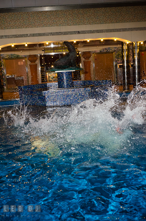 Water splashed after Bride, Groom and Maid of Honor jumped into the swimming pool to trash the dress. Carnival Cruise ship destination wedding reception photos, Cozumel Mexico by photographers of Leo Dj Photography.