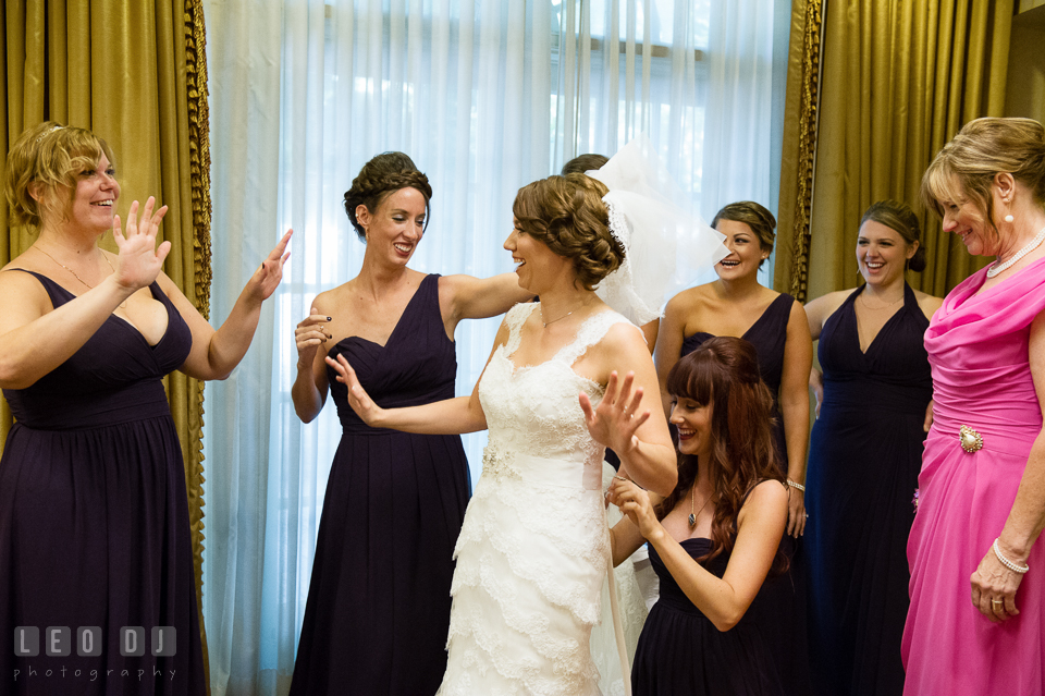 Bride getting into wedding gown with help from the Bridesmaids and her Mother. Historic Inns of Annapolis Maryland, Governor Calvert House Greek wedding, by wedding photographers of Leo Dj Photography. http://leodjphoto.com
